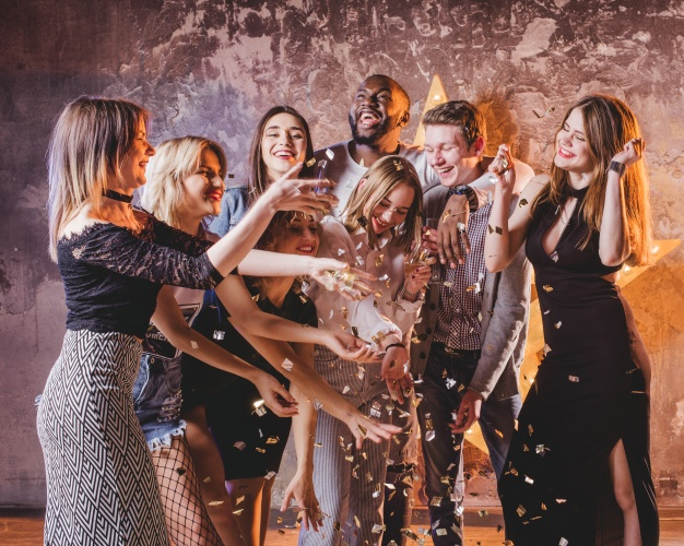 festive-young-friends-having-fun-with-confetti_23-2147651889
